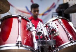 Unrecognizable Afro boy with red jacket attending a drum class and playing