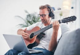 Man playing acoustic guitar in the living room.