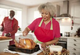 Senior black woman basting a roast turkey in preparation for Christmas dinner, her husband chopping vegetables in the background, front view, close up